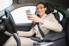 Smiling businesswoman sending a text message Royalty Free Stock Images