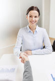 Smiling businesswoman shaking hand in office Stock Images
