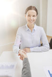 Smiling businesswoman shaking hand in office Royalty Free Stock Image