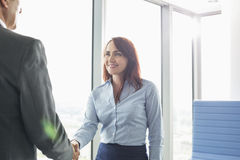 Smiling businesswoman shaking hands with businessman in office Royalty Free Stock Image