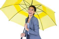 Smiling businesswoman sheltering under umbrella Stock Images