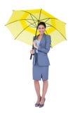 Smiling businesswoman sheltering under umbrella Stock Photos