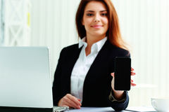Smiling businesswoman showing display of a smartphone Royalty Free Stock Photography