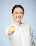 Smiling businesswoman showing a golden plastic card Stock Photo