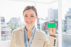 Smiling businesswoman showing green business card Royalty Free Stock Image