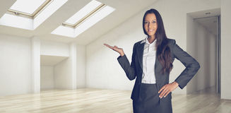 Smiling Businesswoman Showing House Interior. Smiling Businesswoman in Black and White Office Suit Showing House Interior While Looking at the Camera Stock Photography