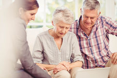 Smiling businesswoman showing laptop monitor to senior couple. At home royalty free stock photography