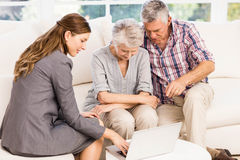 Smiling businesswoman showing laptop monitor to senior couple. At home stock image