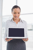 Smiling businesswoman showing laptop screen and looking at it Royalty Free Stock Photo