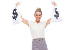 Smiling businesswoman showing money bags Royalty Free Stock Image