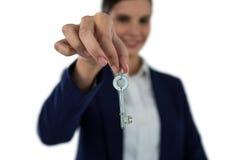 Smiling businesswoman showing new house key. On white background Stock Photo