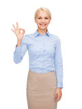 Smiling businesswoman showing ok-sign with hand Stock Photos