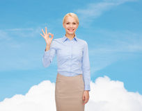 Smiling businesswoman showing ok-sign with hand Royalty Free Stock Images