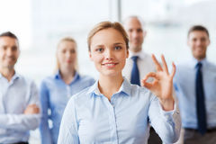 Smiling businesswoman showing ok sign in office Stock Image