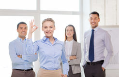 Smiling businesswoman showing ok-sign in office. Office, business and teamwork concept - friendly young smiling businesswoman with team on back showing ok-sign Stock Photography