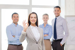 Smiling businesswoman showing ok-sign in office. Office, business and teamwork concept - friendly young smiling businesswoman with team on back showing ok-sign Royalty Free Stock Image
