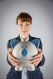 Smiling businesswoman showing piggy bank Stock Images