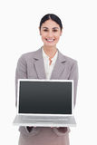 Smiling businesswoman showing screen of her laptop. Against a white background Royalty Free Stock Image