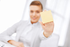 Smiling businesswoman showing sticky note. Business, office, school and education concept - smiling businesswoman showing blank sticky note Royalty Free Stock Photos