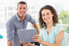 Smiling businesswoman showing tablet to her colleague Royalty Free Stock Images