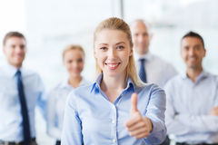 Smiling businesswoman showing thumbs up in office Stock Image