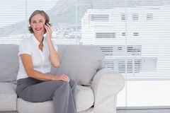 Smiling businesswoman sitting calling in the office Stock Photo