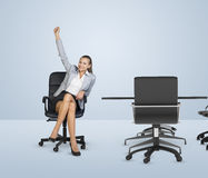 Smiling businesswoman sitting in chair and raising Royalty Free Stock Photos