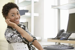 Smiling Businesswoman Sitting At Computer Desk royalty free stock images