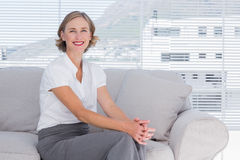 Smiling businesswoman sitting on couch Royalty Free Stock Photos