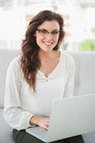 Smiling businesswoman sitting on couch using laptop Stock Photography