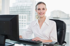 Smiling businesswoman sitting at desk looking at camera Stock Photos