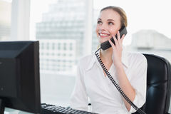 Smiling businesswoman sitting at desk on the phone Stock Photos