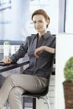 Smiling businesswoman sitting at desk Stock Photos