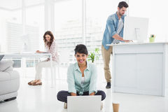 Smiling businesswoman sitting on the floor using laptop Royalty Free Stock Photos
