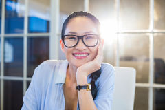 Smiling businesswoman sitting at her desk Stock Photos