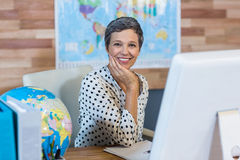 Smiling businesswoman sitting at her desk Stock Images