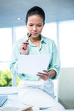 Smiling businesswoman sitting on her desk Royalty Free Stock Photo