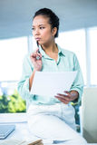 Smiling businesswoman sitting on her desk Stock Image