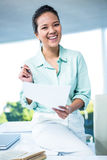 Smiling businesswoman sitting on her desk Stock Photography