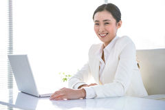 Smiling businesswoman sitting at her desk Stock Image