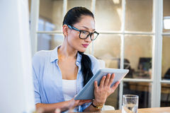 Smiling businesswoman sitting at her desk and working with tablet Stock Photography