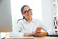Smiling businesswoman sitting at her workplace and holding phone Stock Photo