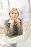 Smiling businesswoman sitting in office Royalty Free Stock Image
