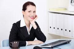 Smiling businesswoman sitting in the office. Royalty Free Stock Photography