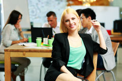 Smiling businesswoman sitting in office Royalty Free Stock Photos