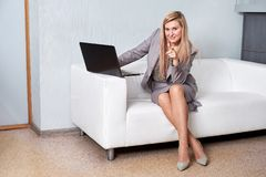 Smiling businesswoman sitting on sofa with laptop computer in office lobby royalty free stock photography