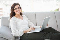Smiling businesswoman sitting on sofa using laptop. In the office Stock Images