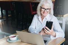 Smiling businesswoman is sitting at table in front of laptop and using smartphone. Pensioner freelancer works. Royalty Free Stock Photos