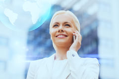 Smiling businesswoman with smartphone outdoors Stock Photography