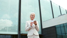 Smiling businesswoman with smartphone outdoors Royalty Free Stock Image